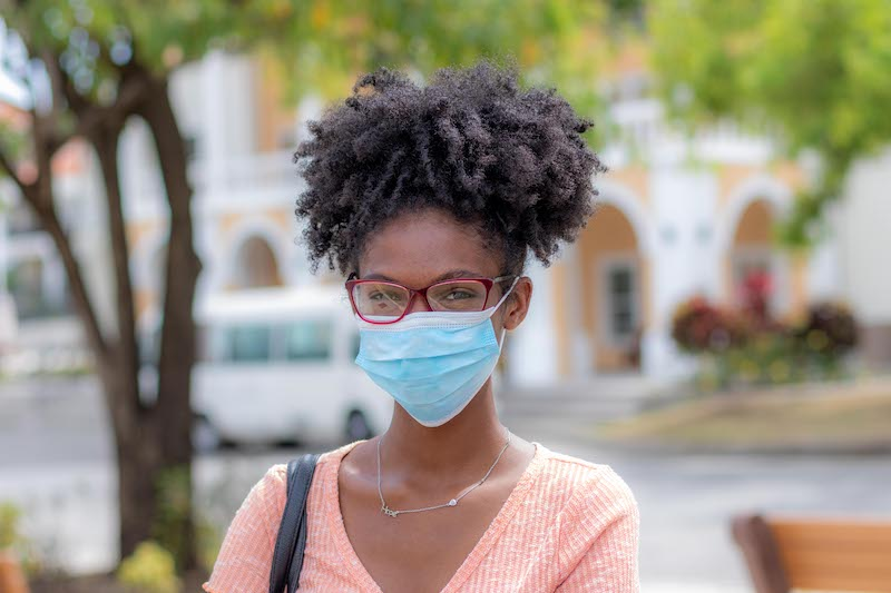 Girl in facial mask standing in front of an SGU building wearing a pink shirt